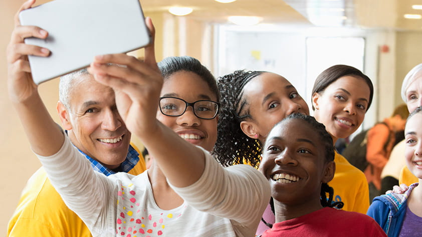 Group of older students and their teacher taking a selfie with a digital tablet