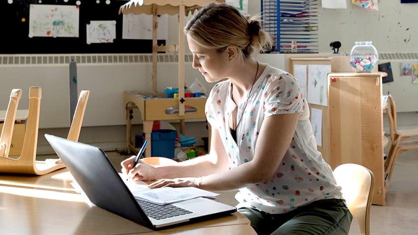 Elementary teacher working on her laptop in her classroom