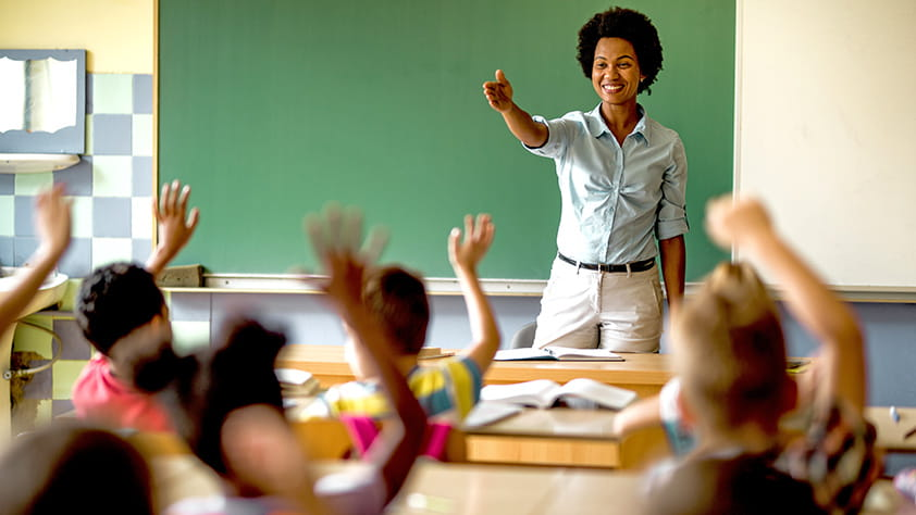 Happy African-American elementary teacher asking questions to her class
