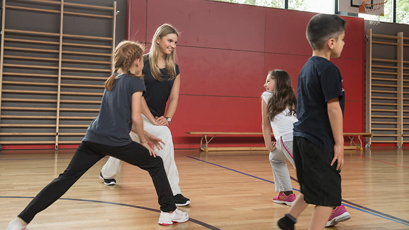 Teacher stretching with her students in a school gym
