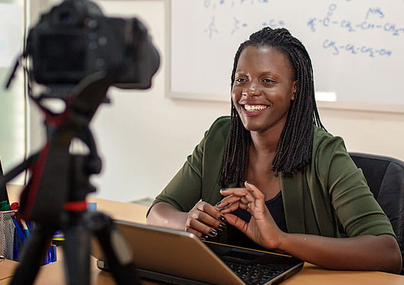 Young Female Teacher Sitting in Front of a Camera Teaching an Online Class