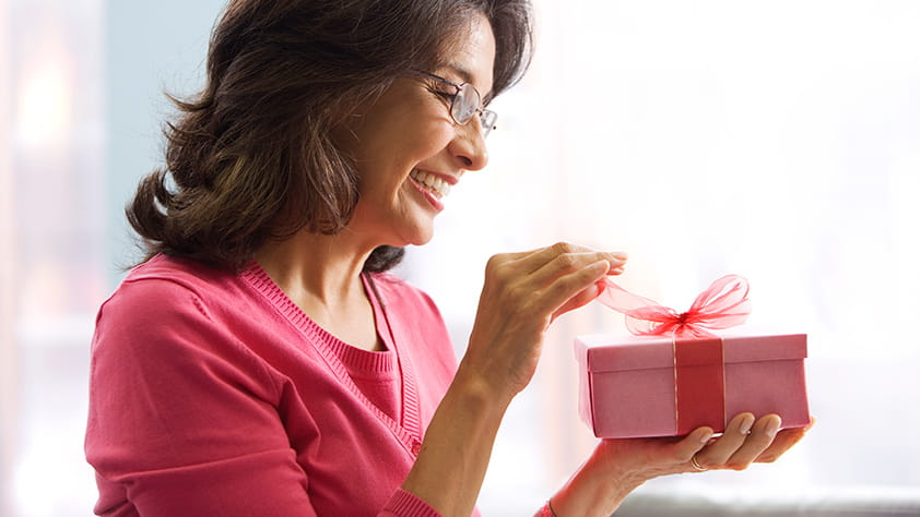 Woman in a red shirt opening a present wrapped with a red bow