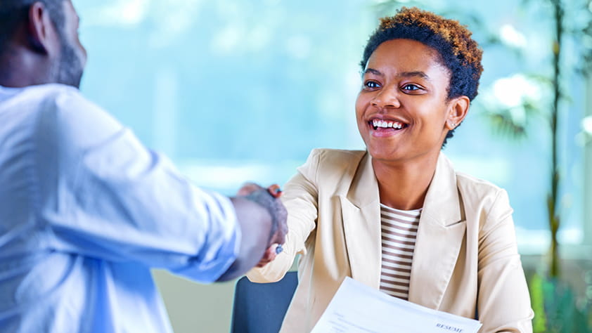 Confident young woman at a job interview, holding her resume and shaking hands with the interviewer