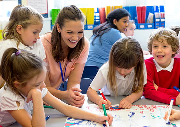 Young teacher sitting at a table with her elementary students