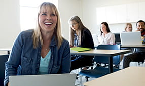 Smiling adult education student using a laptop in a classroom