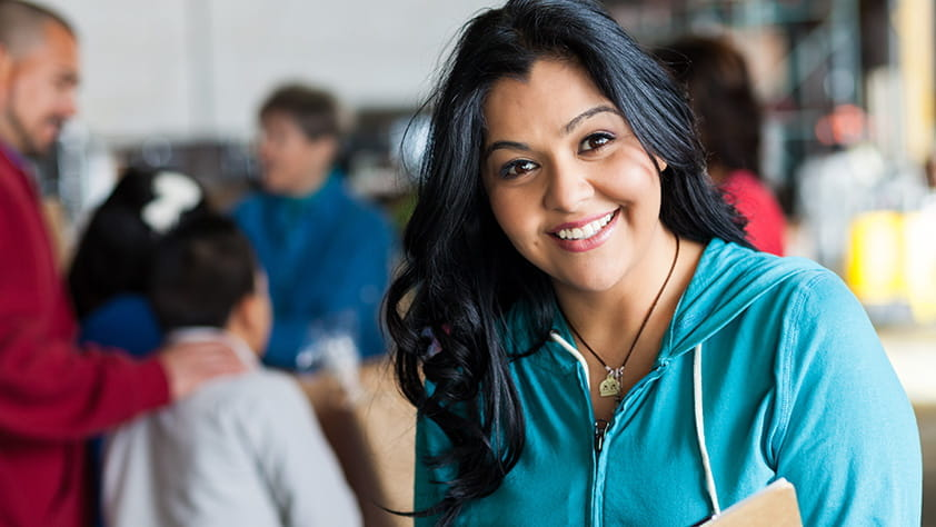 Young Hispanic woman holding a pen and a notebook with families out of focus in the background