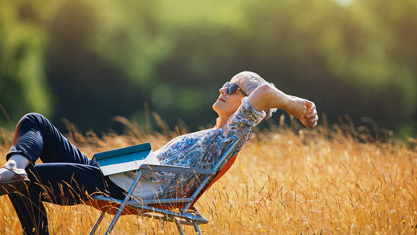 Woman relaxing with book in a sunny field