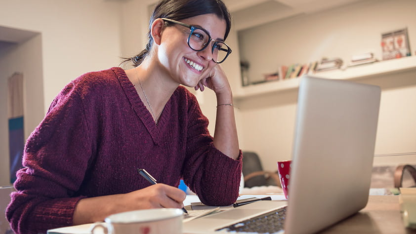Young woman at home using her laptop and writing in a notebook