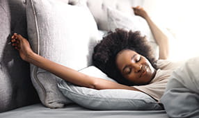 Happy young woman waking up in her bed at home and stretching her arms above her head