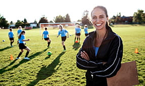 Confident female coach and her middle school girls' soccer team running drills at practice on a sunny field