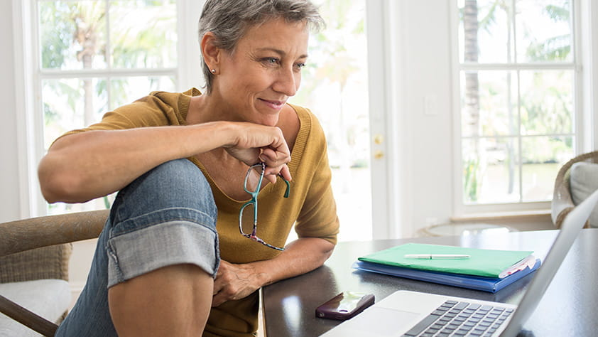 Mature woman using a laptop in her living room