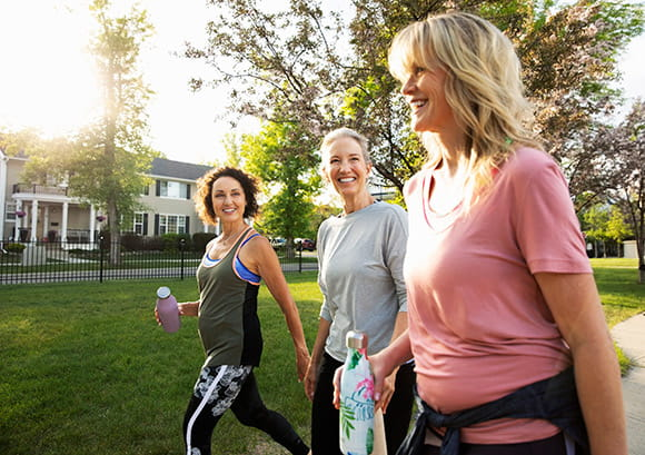 Smiling women walking for exercise in a sunny park