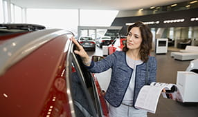 Woman Reviewing New Car at Dealership