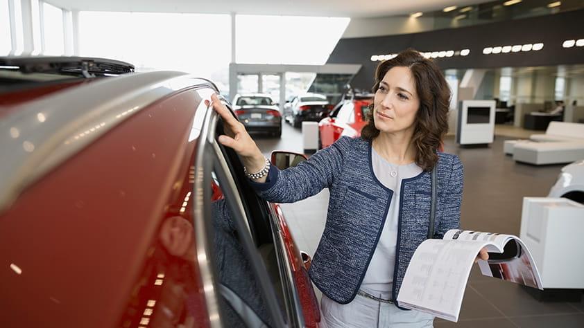 Woman Reviewing New Car at Dealership