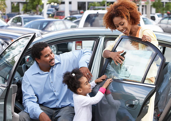 Child Reviewing Sticker Price of New Car at Dealership