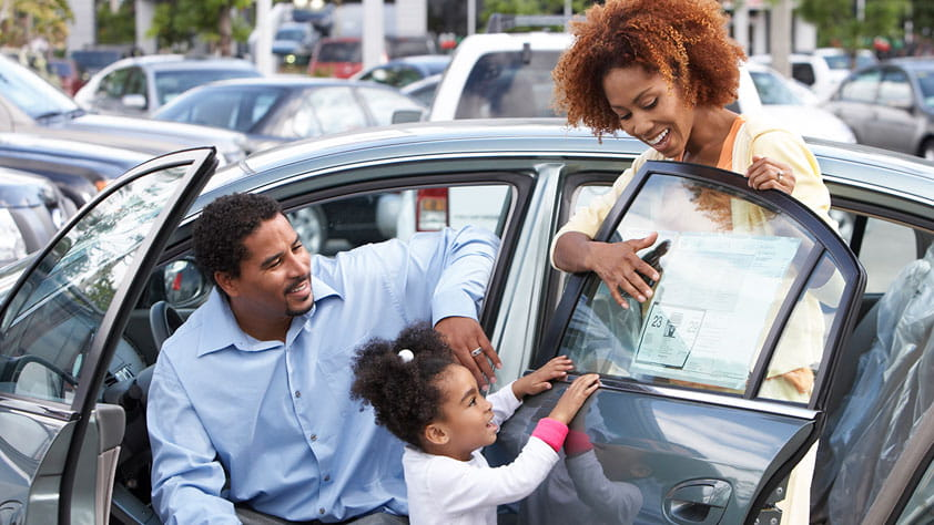 African-American family looking at stats on the window sticker of a new car