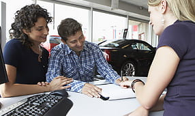 Couple with Car Saleswoman Signing Paperwork