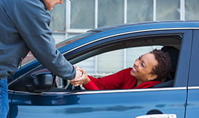 Woman Shaking Hands of Salesman After Purchasing Car