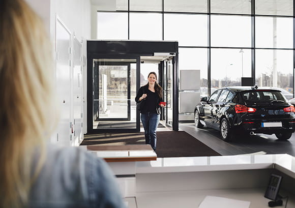 Woman Entering Auto Dealer