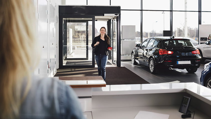 Woman Entering Auto Dealer