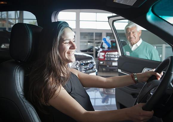 Woman Sitting Behind Wheel of Car in Dealership
