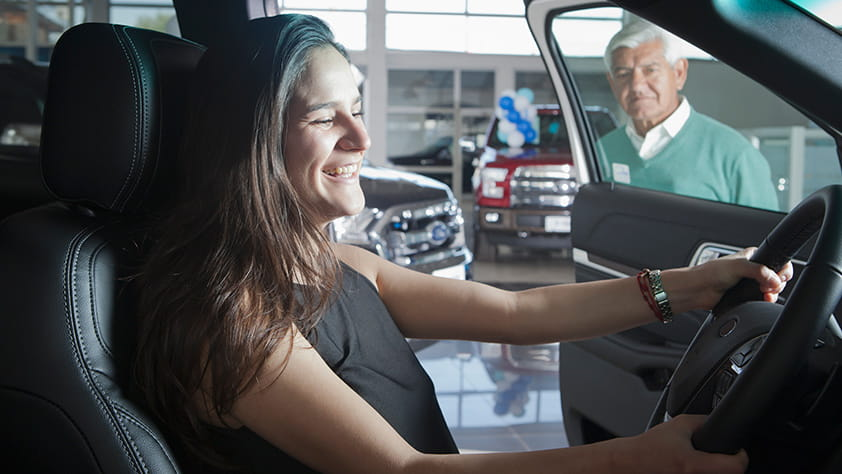 Happy young women sitting behind the wheel of a car at a car dealership