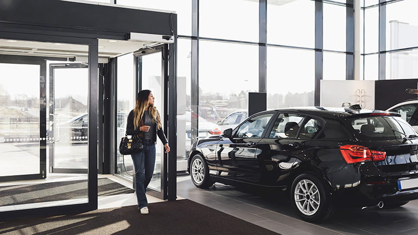 Woman Entering Into New Car Dealership