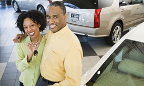 Couple at a Car Dealership Holding the Key to Their New Car