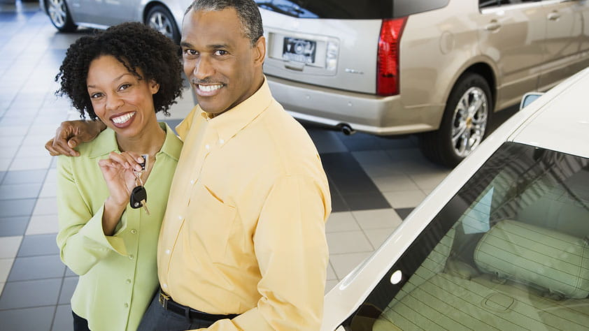 Buy a Car with Confidence Using This 14-Point Checklist - Couple at a Car Dealership Holding the Key to Their New Car