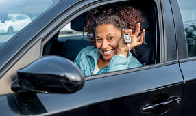 Smiling African-American Woman Sitting in Her New Car Showing Off Car Keys