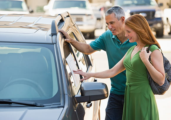 Man and Woman Looking at Car for Sale