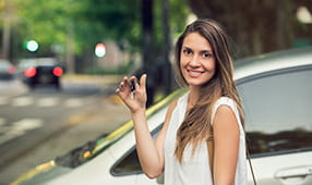 Young woman standing outside next to a car holding a key