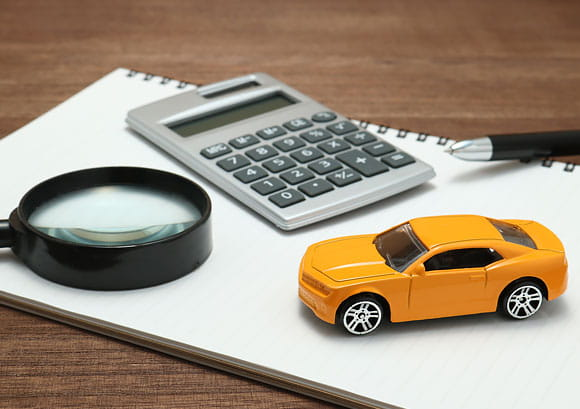 Toy Car, Magnifying Glass, Calculator, Pen and Notebook Sitting on a Desk