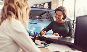 Woman Signing Paperwork at Car Dealership