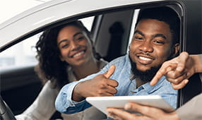 Happy couple gesturing thumbs-up talking with seller in automobile store