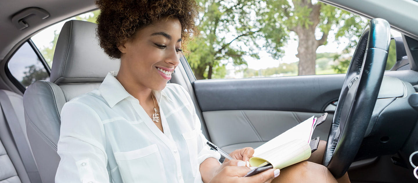 Woman Completing Paperwork in Car