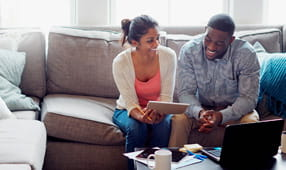 Young couple going through paperwork together on the sofa at home