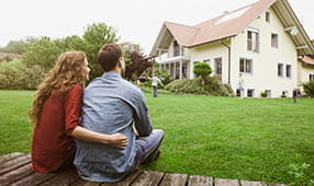 Couple Sitting on Deck Admiring Home