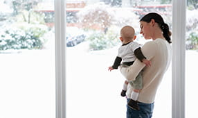 Mom Holding Infant Child Looking Outside Window Onto Winter Scene