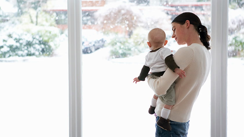 Mom Holding Infant Child Looking Outside Window Onto Winter Scene