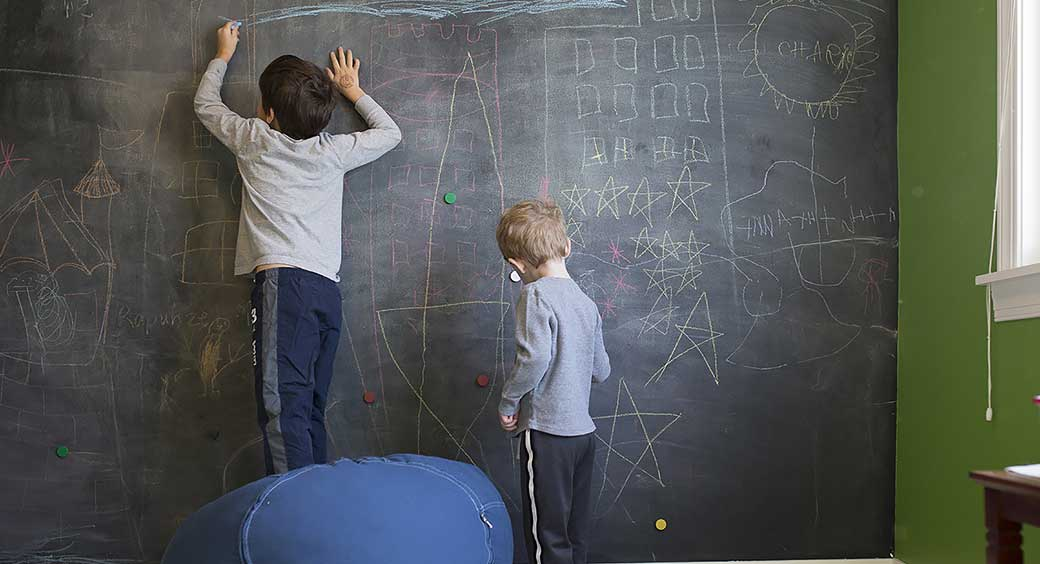 Two Young Boys Drawing on a Chalkboard Wall