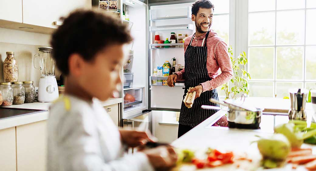 Father Smiling While He Prepares Lunch for Son at Home