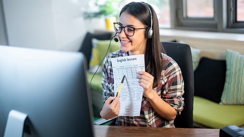 Teacher seated in front of computer at home wearing headset and sharing printed lesson through webcam