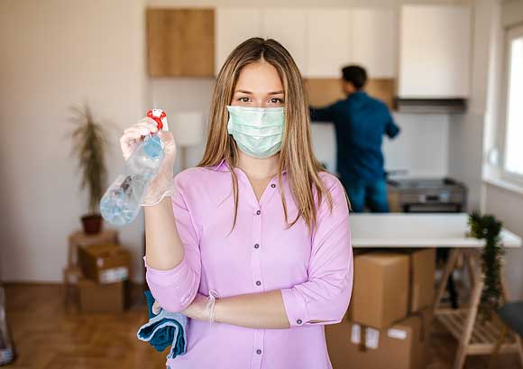 Young Woman Wearing a Mask for COVID-19 protection While Disinfecting Her New House