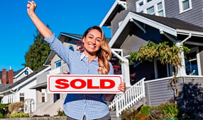 Woman Holding Sold Sign Outside of House