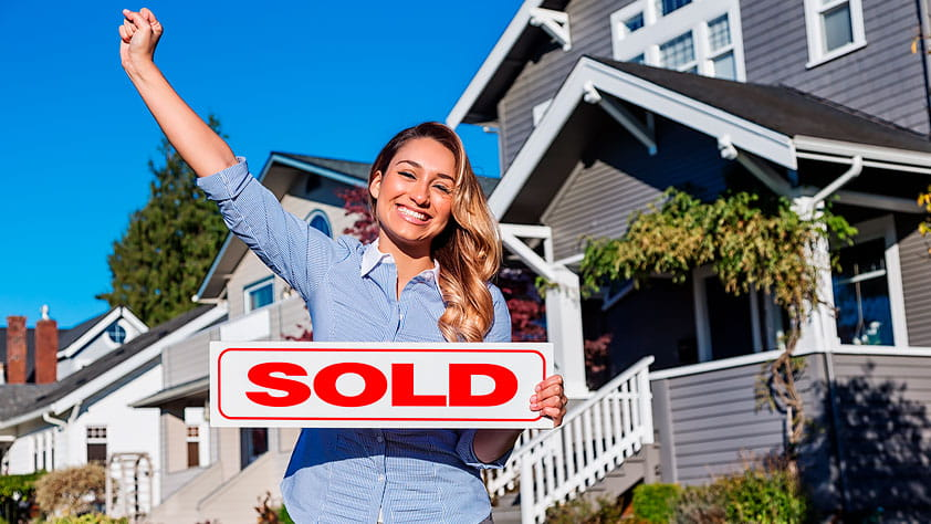 Happy woman with one arm raised and holding a red SOLD sign in the other, standing in front of a row of suburban houses