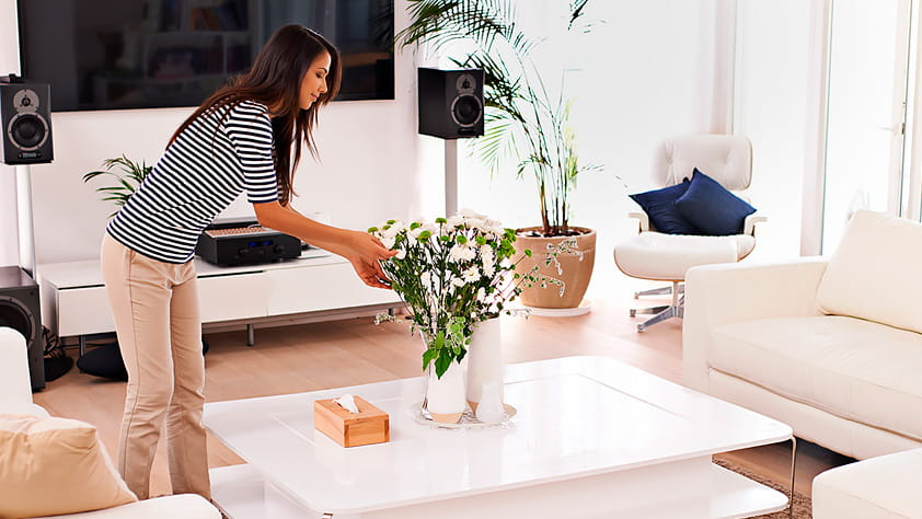 Woman placing a vase of white flowers on her living room table