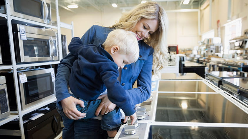 Mom Shopping with Small Child for Kitchen Appliances