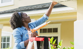 Unexpected Costs of Owning a Home - Woman Fixing Home Exterior