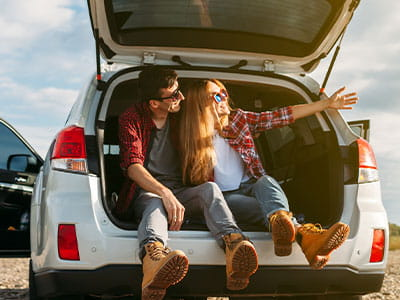 Happy couple on a road trip stop to enjoy the scenery from the hatchback of their insured car